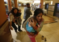 Women ran for safety while carrying children as armed police hunted gunmen who went on a shooting spree in Nairobi's Westgate shopping centre on Sept. 21.